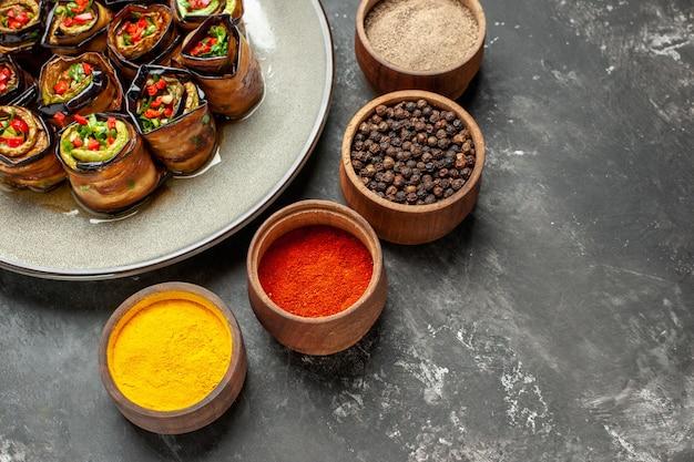 Widok z przodu nadziewane bułeczki z bakłażana na białym owalnym talerzu sól pieprz czerwony pieprz kurkuma na szarym wolnym miejscu