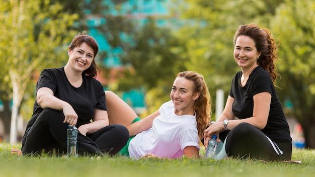 Widok z przodu najlepszych przyjaciół siedzących na trawie w odzieży sportowej