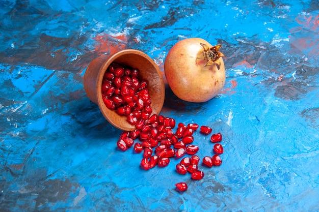Widok z przodu nasiona granatu w małej drewnianej misce granat na niebieskim wolnym miejscu
