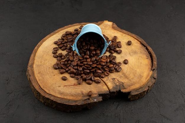 Widok z przodu nasiona kawy brązowe całe świeże na brązowym biurku i ciemnej podłodze