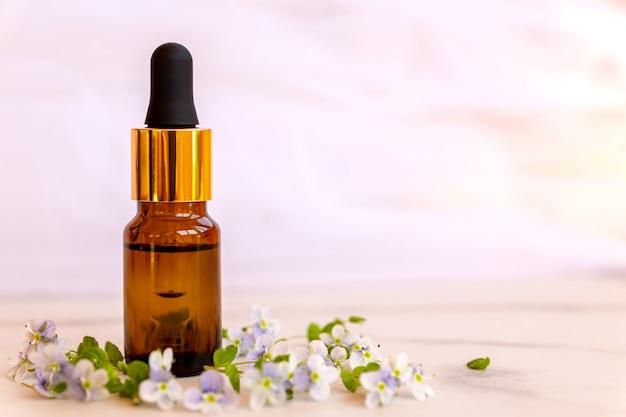 Widok z przodu naturalnego olejku eterycznego w butelce kroplowej na marmurowej powierzchni z dzikimi kwiatami