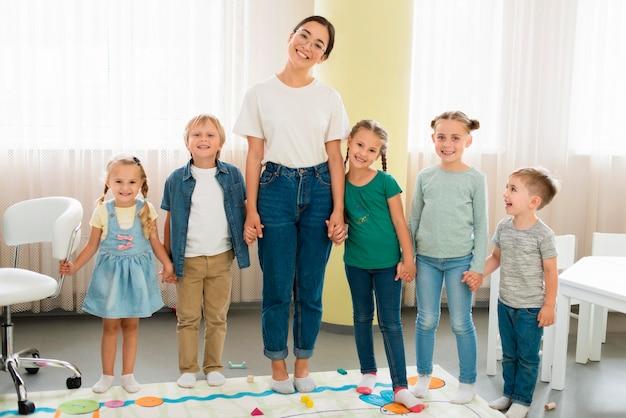 Widok z przodu nauczyciela i dzieci pozujące razem