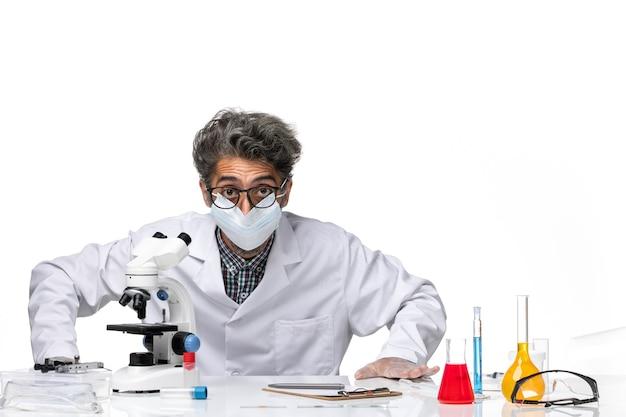 Widok z przodu naukowca w średnim wieku w specjalnym garniturze, siedzącego wokół stołu z rozwiązaniami