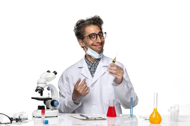 Widok z przodu naukowiec w średnim wieku w białym garniturze medycznym przygotowuje zastrzyk i uśmiecha się