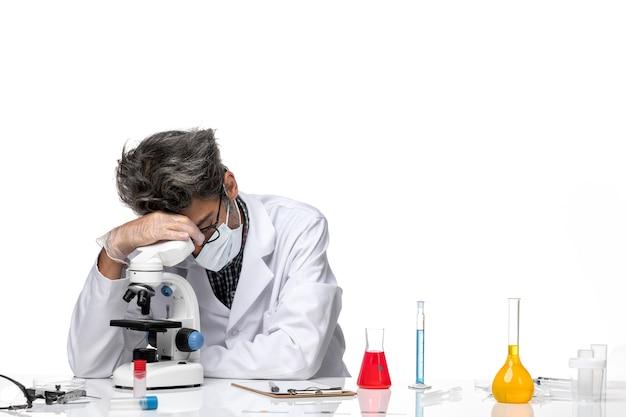 Widok z przodu naukowiec w średnim wieku w białym garniturze medycznym, siedząc i używając mikroskopu