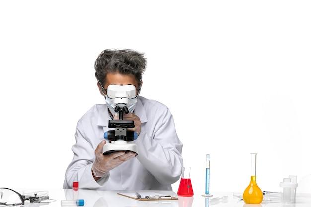 Widok z przodu naukowiec w średnim wieku w białym garniturze medycznym, trzymając mikroskop