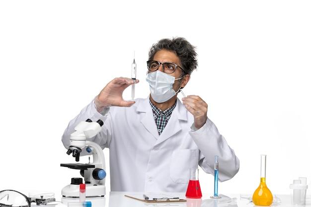 Widok z przodu naukowiec w średnim wieku w białym garniturze medycznym trzymając zastrzyk