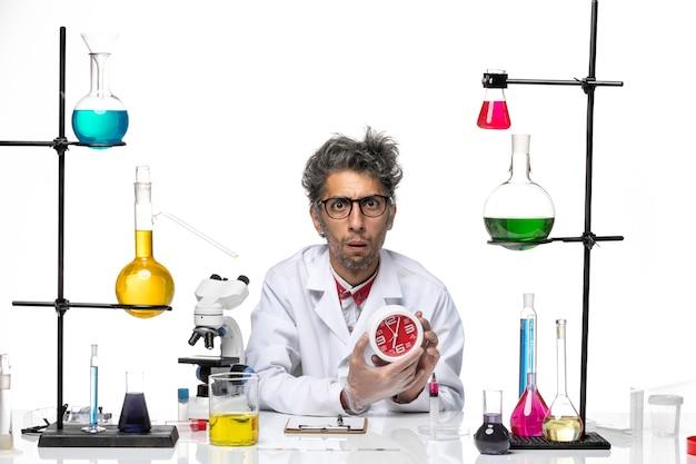Widok z przodu naukowiec w średnim wieku w białym garniturze medycznym, trzymając zegar