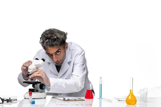Widok z przodu naukowiec w średnim wieku w białym kombinezonie medycznym do mocowania mikroskopu