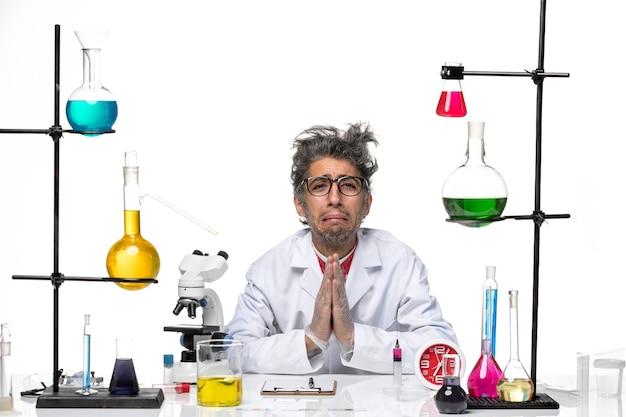 Widok z przodu naukowiec w średnim wieku w garniturze medycznym siedzi i błaga
