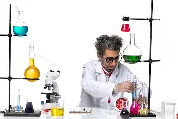 Widok z przodu naukowiec w średnim wieku w kombinezonie medycznym pracujący z różnymi rozwiązaniami