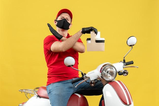 Widok z przodu nerwowego kuriera w czerwonej bluzce i rękawiczkach z kapeluszem w masce medycznej dostarczającego zamówienie siedzącego na skuterze trzymającego rozkazy wykonującego gest stop