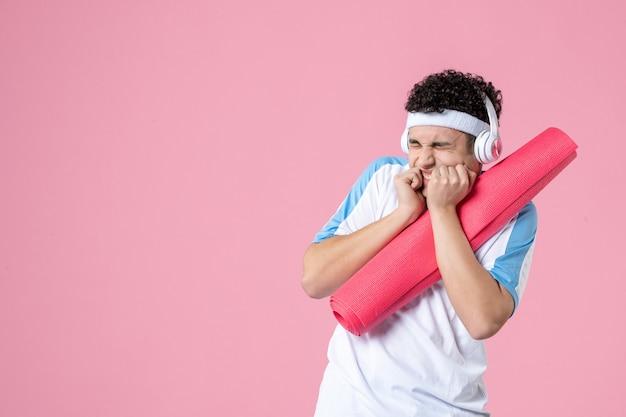 Widok z przodu nerwowy młody mężczyzna w ubraniach sportowych z matą do jogi i słuchawkami
