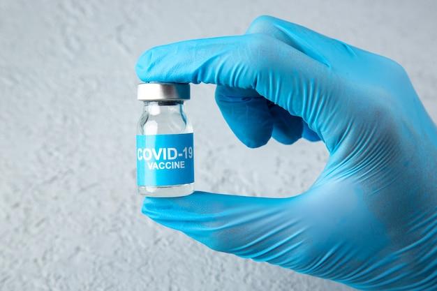 Widok z przodu niebieskiej rękawiczki noszącej dłoń trzymającą zamkniętą ampułkę ze szczepionką przeciw covid na szarym tle piasku