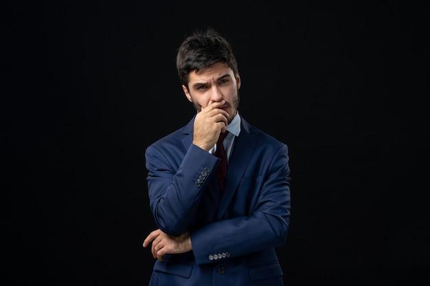 Widok z przodu niepewnego i zdezorientowanego młodego mężczyzny w głębokich myślach na izolowanej ciemnej ścianie
