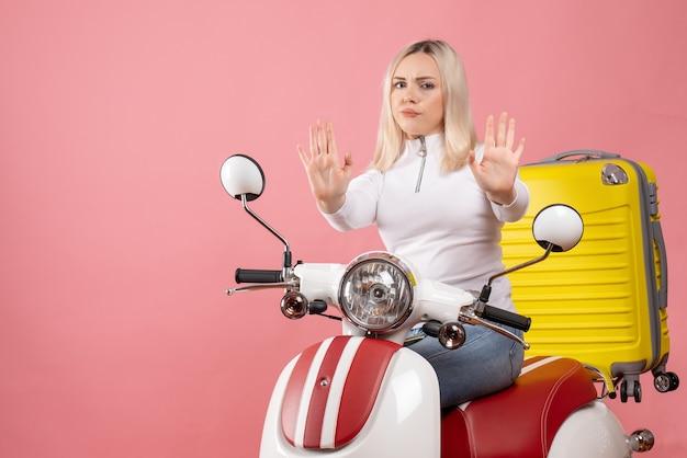 Widok z przodu niezadowolona młoda dama na motorowerze robiącym znak stopu