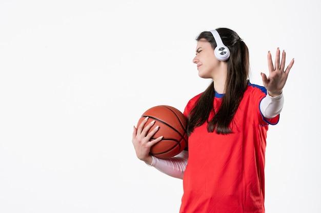Widok z przodu niezadowolona młoda kobieta w strojach sportowych z koszykówką