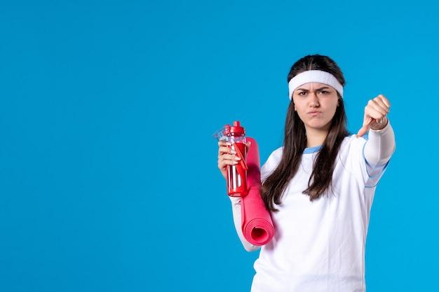 Widok z przodu niezadowolona młoda kobieta z dywanem do ćwiczeń i butelką wody