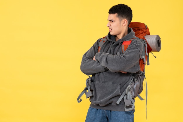 Widok z przodu niezadowolony młody człowiek z czerwonym plecakiem krzyżującym ręce