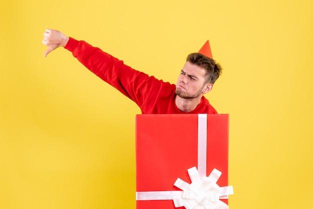 Widok z przodu niezadowolony młody mężczyzna w czerwonej koszuli wewnątrz pudełka