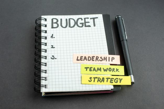 Widok z przodu notatki budżetowej w notatniku z piórem na ciemnym tle