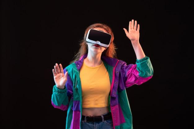 Widok z przodu nowoczesna młoda dama w kolorowej koszulce z pomarańczowym płaszczem, grająca i próbująca wyrażenia rąk vr, porusza się na czarnym tle interaktywna gra