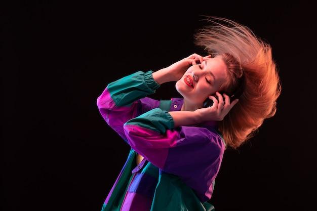 Widok z przodu nowoczesna młoda dama w kolorowym pomarańczowym płaszczu z czarnymi słuchawkami pozuje do słuchania muzyki na czarnym tle tańczy nowoczesną modę