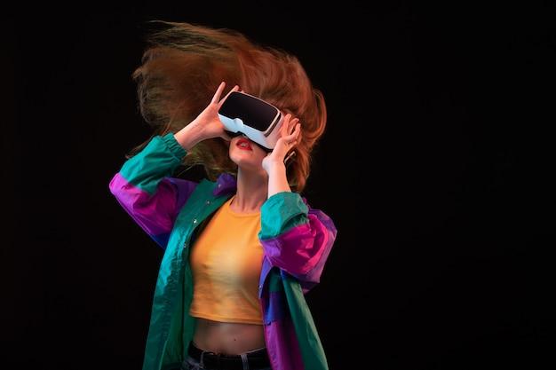Widok z przodu nowoczesnej młodej damy w pomarańczowej koszulce w kolorowym płaszczu, grającej w wirtualną rzeczywistość na czarnym tle interaktywnej gry