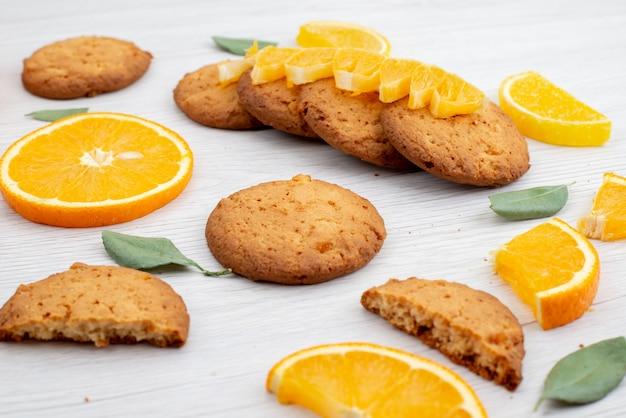 Widok z przodu o smaku pomarańczowym ciasteczka ze świeżych pomarańczowych plasterków na lekkim biurku ciasteczka owocowe