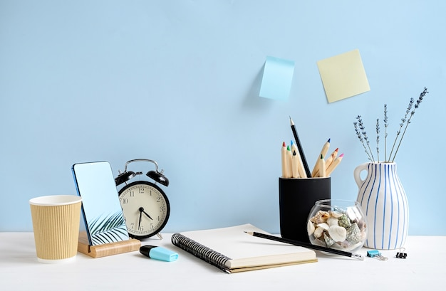 Widok z przodu obszaru roboczego z notatnikiem, telefonem, ołówkami, kawą, zegarem na białym stole nad niebieską ścianą. makieta z miejscem na kopię
