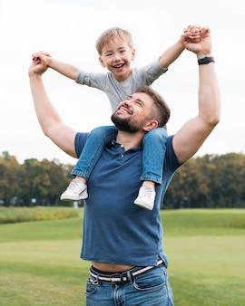 Widok z przodu ojca trzymającego syna na ramionach