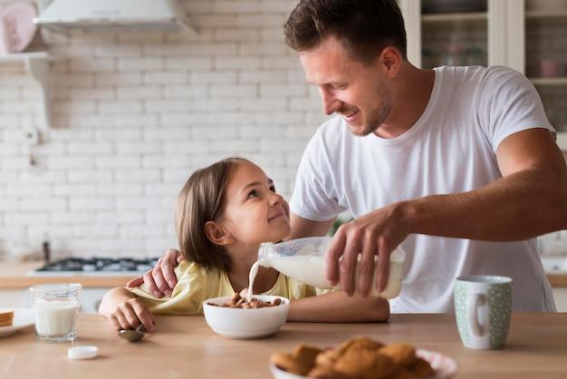 Widok z przodu ojciec nalewa mleko do miski