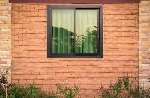 Widok z przodu okna na zewnątrz na mur z cegły