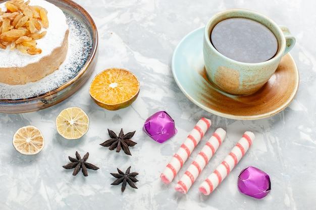 Widok z przodu okrągłe małe ciasto cukrowe w proszku z rodzynkami, herbatą i cukierkami na białej powierzchni