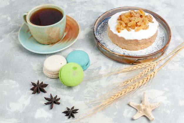 Widok z przodu okrągłe małe ciasto cukrowe w proszku z rodzynkami, herbatą i francuskimi makaronikami na białej powierzchni ciasto z kremem cukrowym słodkie biszkopty