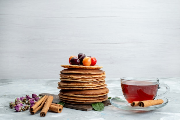 Widok z przodu okrągłe naleśniki pieczone i pyszne z herbatą wiśniową na lekkim biurku ciasto owocowe