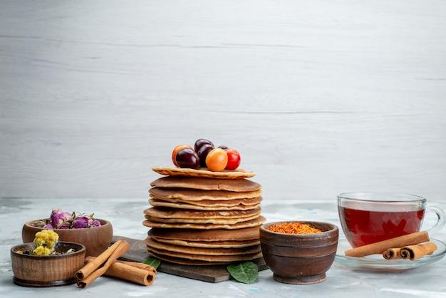 Widok z przodu okrągłe naleśniki pieczone i pyszne z wiśniami, cynamonem i herbatą na lekkim biurku ciasto owocowe