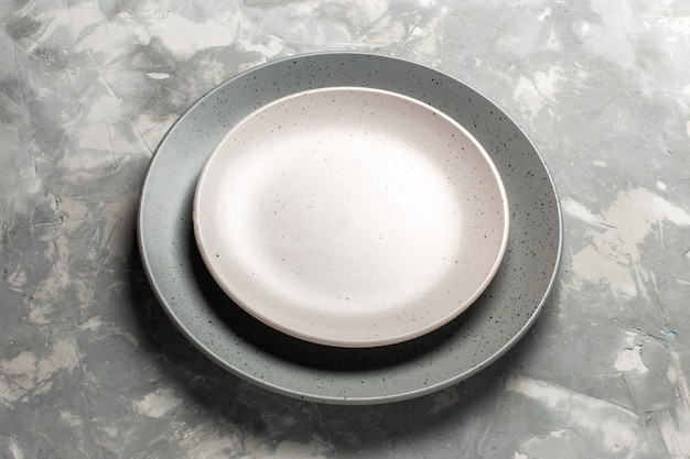 Widok z przodu okrągły pusty talerz w kolorze szarym z białym talerzem na szarym biurku.