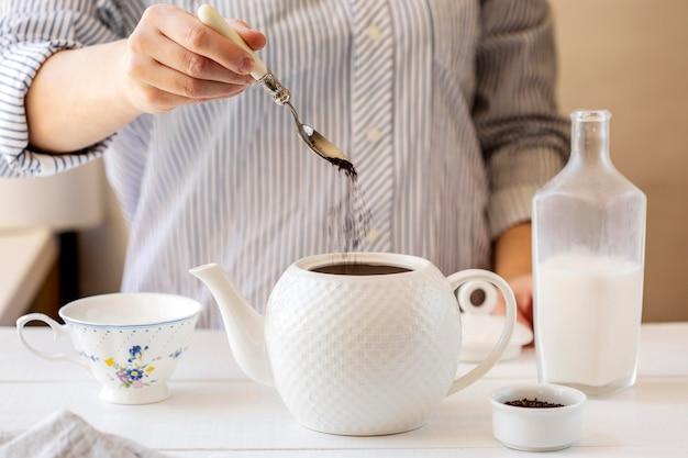 Widok z przodu osoby przygotowującej herbatę mleczną