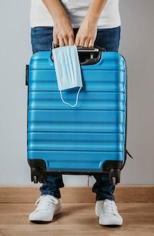 Widok z przodu osoby trzymającej bagaż i maskę medyczną
