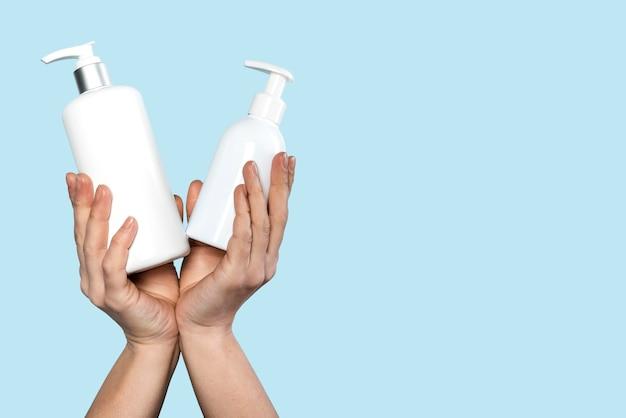 Widok z przodu osoby trzymającej butelki ze środkiem dezynfekującym i mydłem