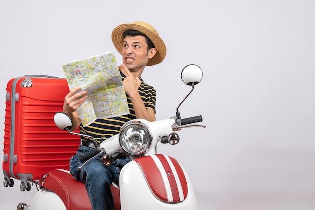 Widok z przodu oszołomionego młodego człowieka w słomkowym kapeluszu na mapie gospodarstwa motoroweru