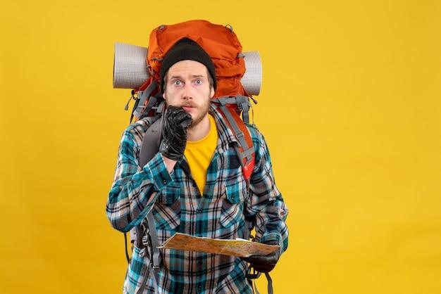 Widok z przodu oszołomionego młodego turysty ze skórzanymi rękawiczkami i plecakiem z mapą