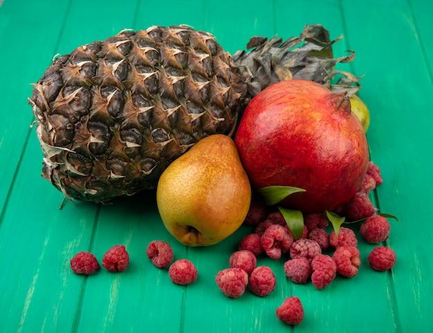 Widok z przodu owoców jak granat brzoskwini ananas i maliny na zielonej powierzchni