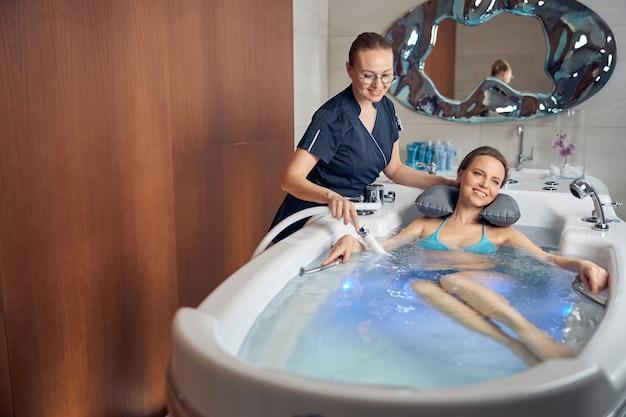 Widok z przodu pacjenta leżącego w wannie podczas hydromasażu w salonie spa