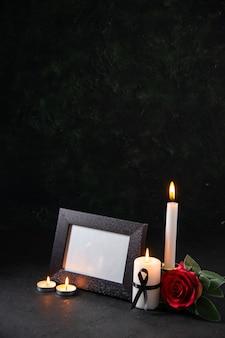 Widok z przodu palących się świec z ramką na zdjęcie na ciemnej powierzchni