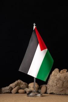 Widok z przodu palestyńskiej flagi z różnymi kamieniami w ciemności
