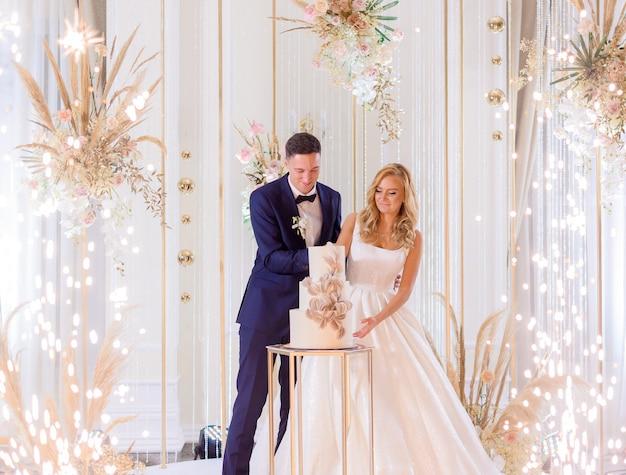 Widok z przodu panny młodej i pana młodego, stojących na jasnej scenie z dekoracją tnącą razem tort weselny