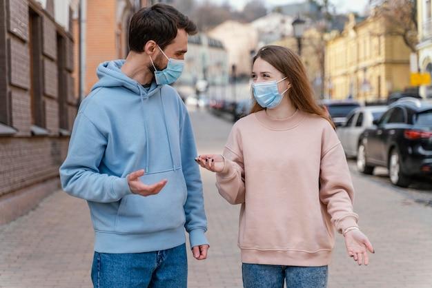 Widok z przodu para ubrana w maskę medyczną w mieście
