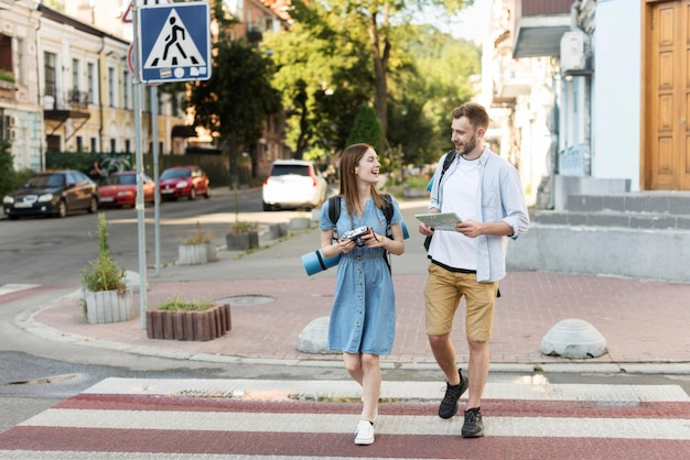 Widok z przodu pary turystycznej z mapą i aparatem na przejściu dla pieszych